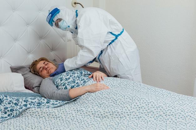 Ppeを身に着けている医師は、自宅のベッドでcovidを持つ眠っている女性に出席します