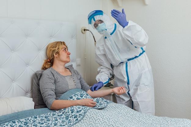 Ppeを身に着けている医師が自宅のベッドでcovidを持つ女性に出席します