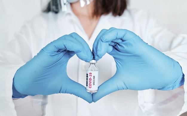 Доктор в синих латексных перчатках показывает лекарство от коронавируса
