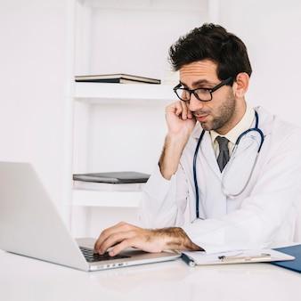 Doctor wearing eyeglasses using laptop