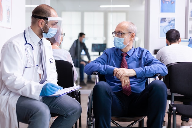 Doctor wearing face mask and visor against infection with coronavirus while talking with disabled senior man in waiting area sitting on wheelchair