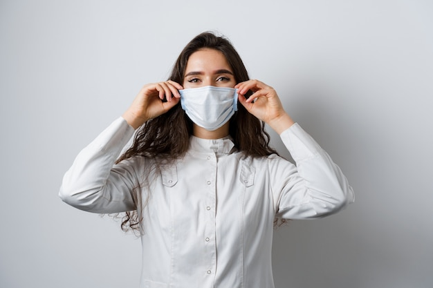 Doctor wearing medical mask on white background. young attractive woman in medical robe. quarantine coronavirus covid-19 trends.
