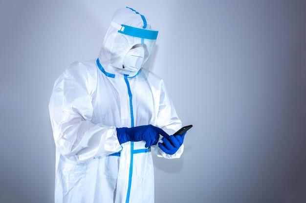 의료 보호 복, 고글, 마스크, 장갑을 착용 한 의사가 전화를 겁니다. 바이러스 전염병에 의한 보호 메르 스. 코로나 바이러스 (코로나 19). 건강 관리 개념.