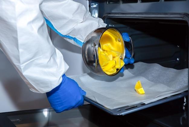 医療用防護服、ゴーグル、マスク、手袋を着用して食事を準備する医師。オーブンでジャガイモ。ウイルスの流行による保護マー。コロナウイルス(covid-19)。ヘルスケアのコンセプト。