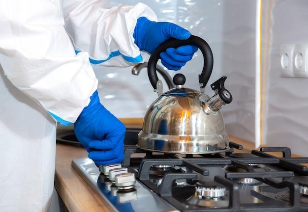 医療用防護服、ゴーグル、マスク、手袋を着た医師が台所でお茶を準備している。ガスコンロのティーポット。ウイルスの流行による保護マー。コロナウイルス(covid-19)。ヘルスケアのコンセプト。
