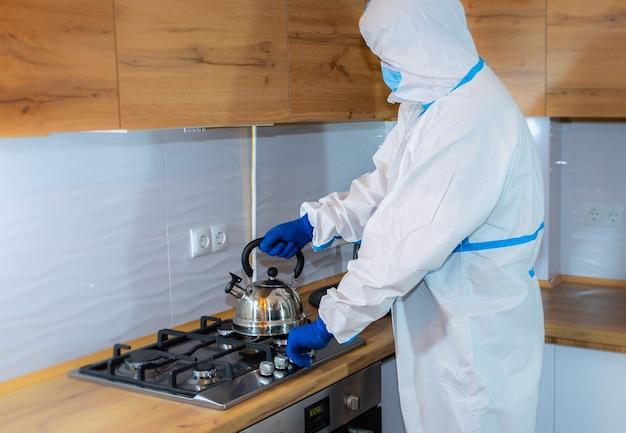 의료 보호복, 고글, 마스크, 장갑을 끼고 부엌에서 차를 준비하는 의사. 가스 렌지에 주전자입니다. 바이러스 전염병에 의한 보호 메르스. 코로나 바이러스 (코로나 19). 의료 개념입니다.