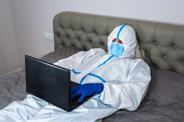 医療用防護服、ゴーグル、マスク、手袋を着た医師が、自宅のベッドに横たわってラップトップで作業しています。ウイルスの流行による保護マー。コロナウイルス(covid-19)。ヘルスケアのコンセプト。