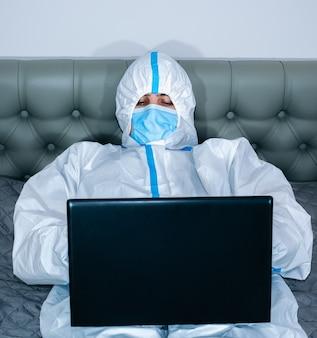 医療用防護服、ゴーグル、マスク、およびラップトップで作業する手袋を着用し、自宅のベッドに横たわっている医師。ウイルスの流行による保護は重要です。コロナウイルス(covid-19)。ヘルスケアの概念。