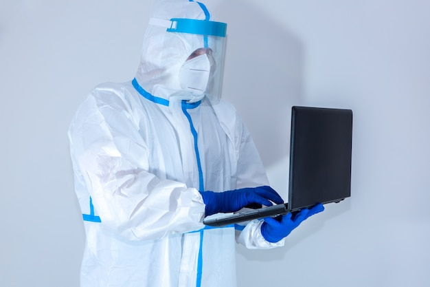 医療用防護服、ゴーグル、マスク、手袋を着用した医師がノートパソコンで作業しています。ウイルスの流行による保護マー。コロナウイルス(covid-19)。ヘルスケアのコンセプト。