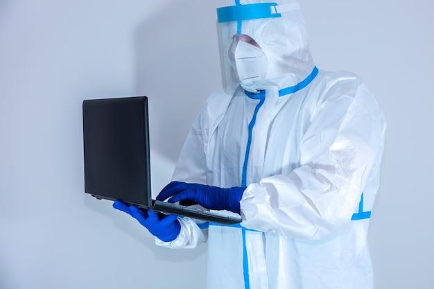 ノートパソコンで作業する医療用防護服、ゴーグル、マスク、手袋を着用した医師。ウイルスの流行による保護は重要です。コロナウイルス(covid-19)。ヘルスケアの概念。