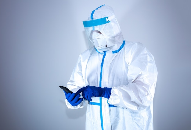 Doctor wearing medical protective suit, goggle, mask, and gloves call on phone. protection mers by virus epidemic. coronavirus (covid-19). healthcare concept.