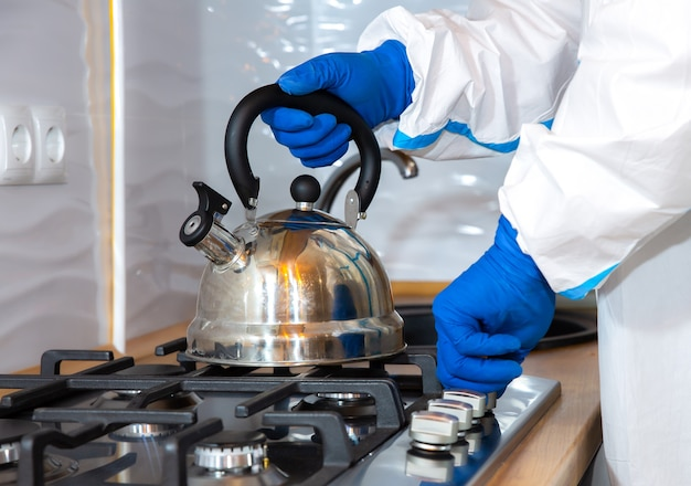Doctor wearing medical protective suit, goggle, mask, and gloves preparing tea on the kitchen. teapot on the gas stove. protection mers by virus epidemic. coronavirus (covid-19). healthcare concept.