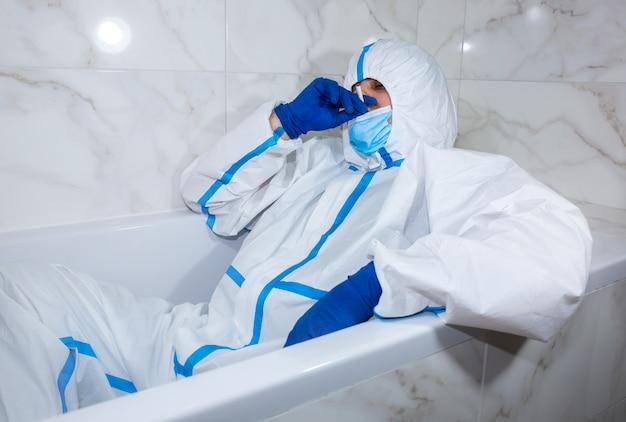 お風呂に横たわる医療用防護服、マスク、手袋を着用した医師。仕事の後にリラックス。ウイルスの流行による保護マー。コロナウイルス(covid-19)。ヘルスケアのコンセプト。