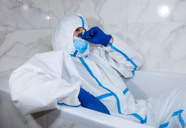 お風呂に横たわっている医療用防護服、マスク、手袋を着用した医師。仕事の後にリラックスしてください。ウイルスの流行による保護は重要です。コロナウイルス(covid-19)。ヘルスケアの概念。