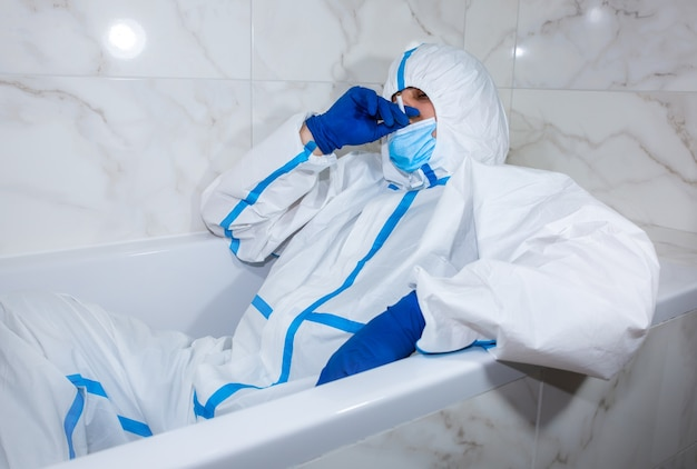 Doctor wearing medical protective suit, mask, and gloves lying in the bath. relax after work. protection mers by virus epidemic. coronavirus (covid-19). healthcare concept.