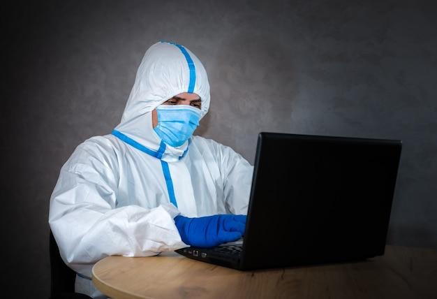 ノートパソコンで作業する医療用防護服、医療用マスク、手袋を着用した医師。ウイルスの流行による保護は重要です。コロナウイルス(covid-19)。ヘルスケアの概念。パンデミック・コビッドでのリモートワーク。
