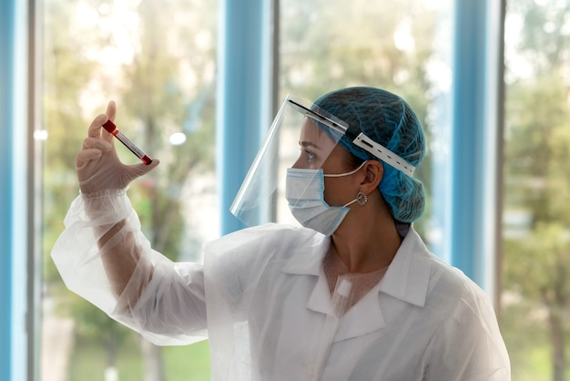 Doctor wearing personal protective equipment looking at a test tube labeled coronavirus