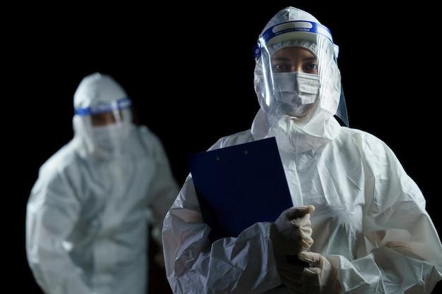 Ppe와 코로나 / covid-19 바이러스 실험실 보고서를 손에 들고 얼굴 방패를 착용하는 의사.