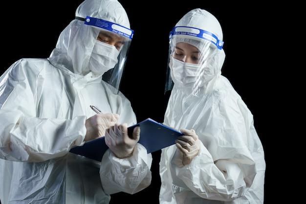 Ppe와 안면 보호대를 착용하고 코로나 / covid-19 바이러스 실험실 보고서를 찾는 의사.