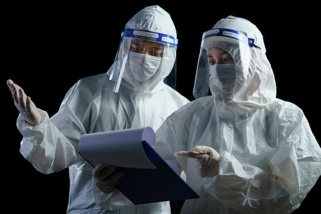 Ppe와 코로나 / covid-19 바이러스 실험실 보고서에 대해 이야기하는 얼굴 방패를 착용하는 의사.