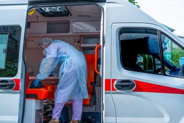 Доктор, носящий защитную одежду от коронавируса в машине скорой помощи