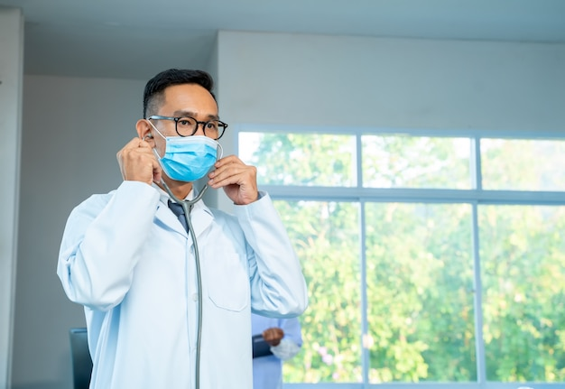 Doctor wearing protective mask to protect against covid-19 standing with stethoscope at hospital, healthcare and medicine concept.