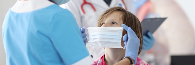 Doctor wearing protective mask puts on mask for little girl