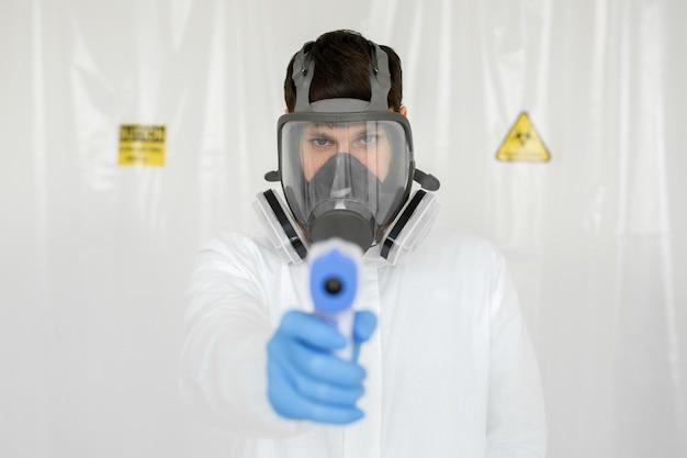 赤外線額温度計を使用する準備ができている防護マスクを身に着けている医者
