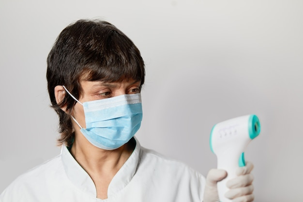 Doctor wearing protective mask use infrared forehead thermometer  to check body temperature for virus symptoms.