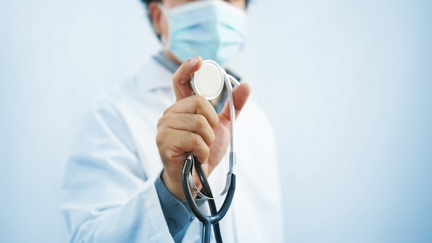 Doctor wearing protective mask with stethoscope in hand and, healthcare and medical concept.