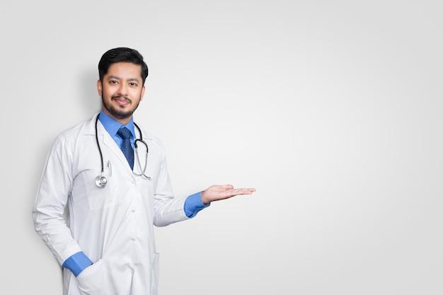 コピースペースで白い壁に隔離されたプレゼンテーションとポインティングしながら制服笑顔を着て医師