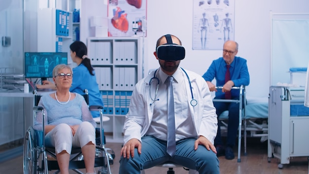 Doctor wearing vr headset, diagnosing senior woman problems while she sitts in a wheelchair in the back. futuristic medicine, health care of the future in private clinic or hospital