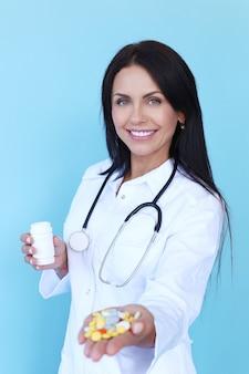 Доктор в белом халате и стетоскопе с таблетками
