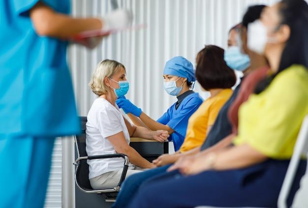 医師は白人女性にワクチンを注射するフェイスマスクを着用し、看護師は列に並んで座っている女性患者から個人情報を取得し、ぼやけた前景で19回の予防接種を行います。