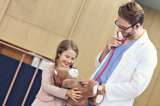 Doctor welcoming little girl in clinic