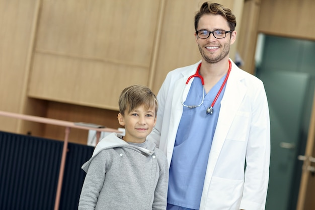 Doctor welcoming young boy in clinic