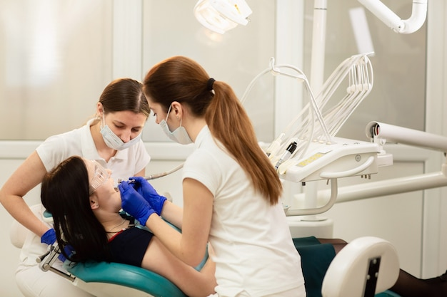 Doctor whit assistant treating teeth of patient, preventing caries. stomatology concept