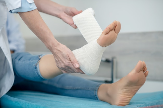Doctor in white coat bandaging foot of patient in jeans on couch, faces are not visible