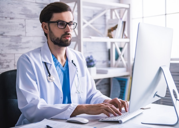 Doctor in white coat and eyeglasses is using a computer.
