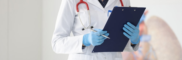 Doctor in white coat and gloves holds pen and clipboard