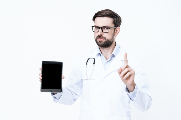 The doctor in a white coat holds a tablet in his hands.