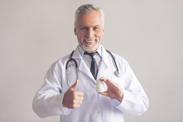 Doctor in white coat is holding a bottle of medicine.