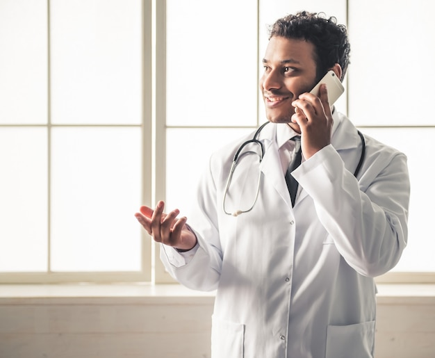 Doctor in white coat is talking on the mobile phone.