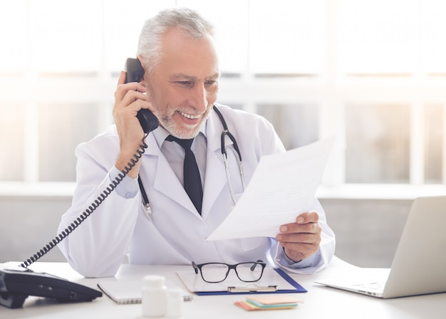 Doctor in white coat is talking on the phone