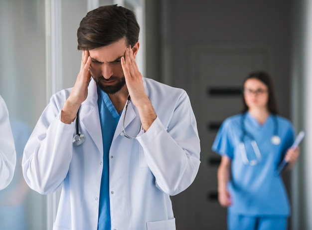 Doctor in white coat is touching his temples.