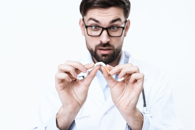 Doctor in a white coat smears a cigarette.