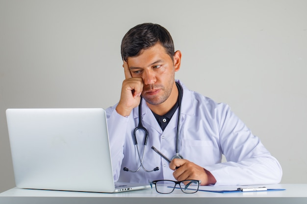 Doctor in white coat, stethoscope sitting and looking at laptop and looking careful