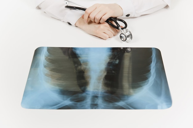 Doctor at white desk with x-ray of lungs, fluorography, roentgen in light office in hospital. woman holds in hands stethoscope. medicine concept