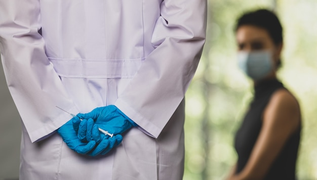 Doctor in white lab coat and blue rubber gloves hold and hiding vaccine syringe needle in hand behind back before walking to female patient who sitting and waiting frightened in blurred background.