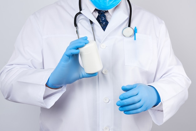 Doctor in a white medical coat and blue latex gloves holds a white plastic jar of pills